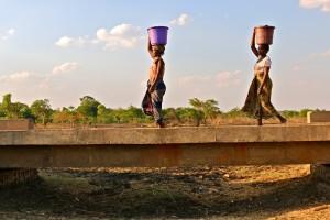 Två kvinnor bär vatten över bron och floden som har torkat.